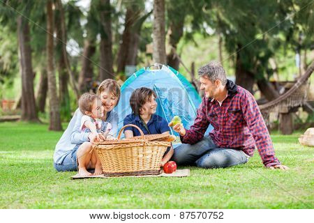 Happy family of four with picnic basket at campsite