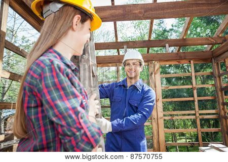 Smiling male and female construction workers holding ladder in wooden cabin at site