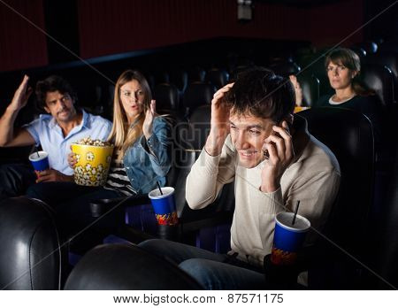 Spectators shouting at man using mobilephone while watching film in movie theater
