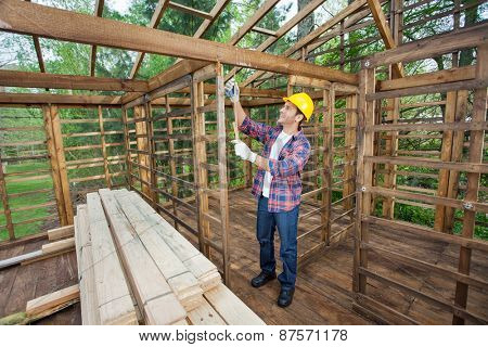 Full length of male worker taking measurements in timber cabin at construction site