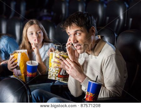Annoyed daughter giving shh expression to father using mobilephone in cinema theater