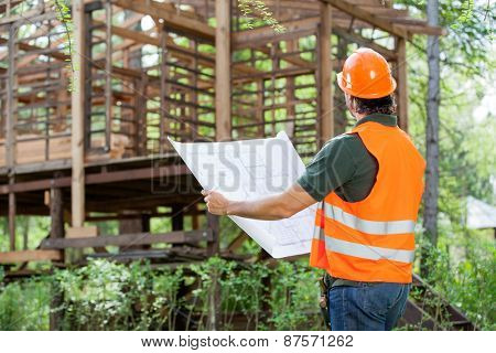 Male architect with blueprint examining wooden cabin at construction site