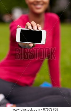 fitness, people, technology and sport concept - close up of smiling african american woman showing smartphone outdoors