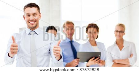 attractive businessman in office showign thumbs up