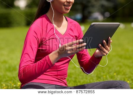 fitness, technology, people and sport concept - close up of smiling african american woman with tablet pc computer sitting on mat outdoors
