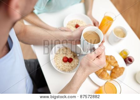 food, eating, people and healthy food concept - close up of couple having breakfast at home