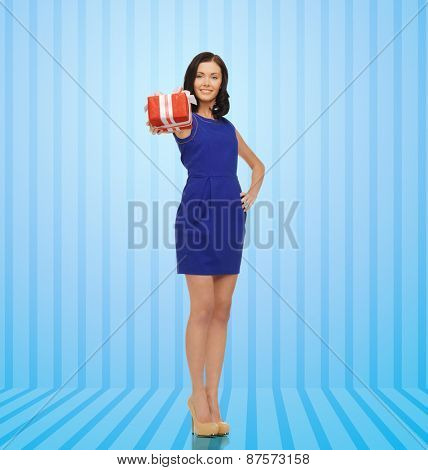 people, holidays, greetings, gifts and shopping concept - happy young woman in blue dress with present over blue striped background