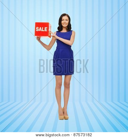 people, business, retail, shopping and consumerism concept - happy young woman in dress with red sale sign over blue striped background