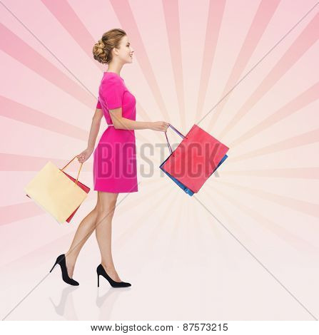 people, retail, sale and consumerism concept - happy young woman in dress with red shopping bags sign over pink burst rays background