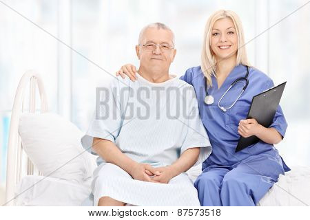 Young female doctor and a mature patient posing seated on a hospital bed