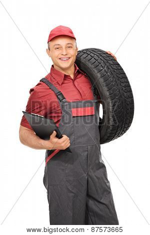 Vertical shot of a male manual worker in a gray jumpsuit holding a clipboard and a tire isolated on white background
