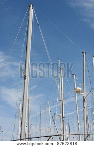 Sail boat masts against a blue sky. Closeup of the masts of boats in storage for the winter, in vertical format.