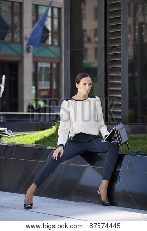 Young beautiful business woman sitting on a bench in the sunny city