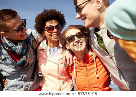 tourism, travel, people, leisure and teenage concept - group of happy friends in sunglasses hugging and laughing on city street