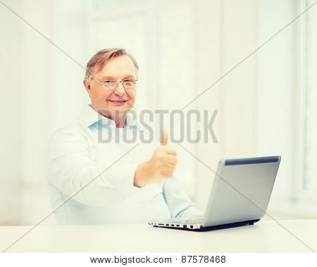technology, oldness and lifestyle concept - old man in eyeglasses with laptop computer at home showing thumbs up