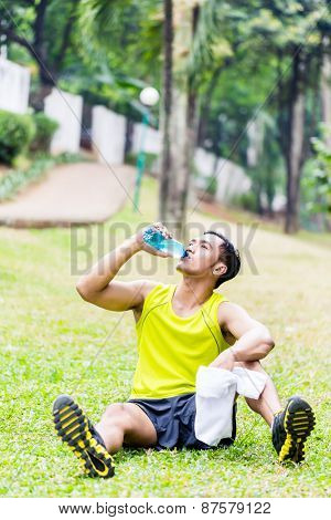 Asian man having break from sport training in tropical park, drinking water from a bottle