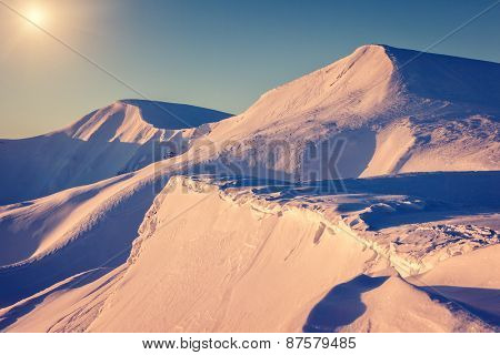 Mountain range glowing by warm sunlight at twilight. View from ski resort Dragobrat. Dramatic morning scene. Carpathian, Ukraine, Europe. Beauty world. Retro and vintage toning effect.