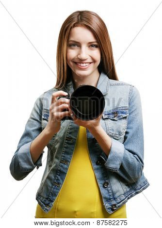 Young female photographer taking photos on grey background