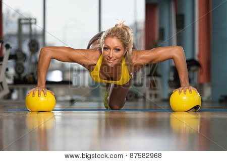 Woman Doing Push Up Exercise On Yellow Balls