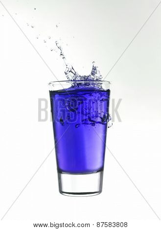 Splash in a glass of blue lemonade isolated on white background