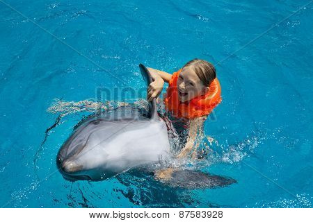 Happy Little Girl Riding The Dolphin In Swimming Pool.