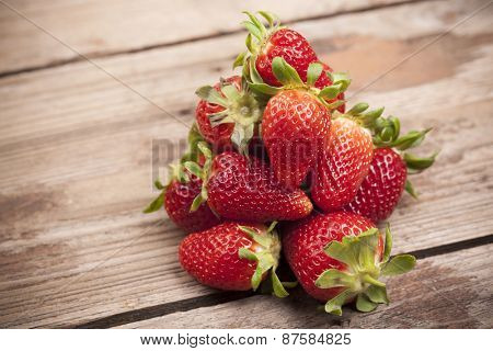 Ripe strawberries on wooden background