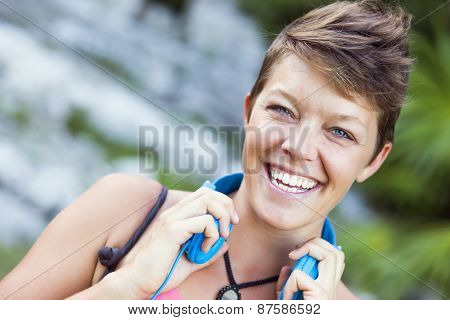 Woman with short hair and yoga mat outdoors with headphones