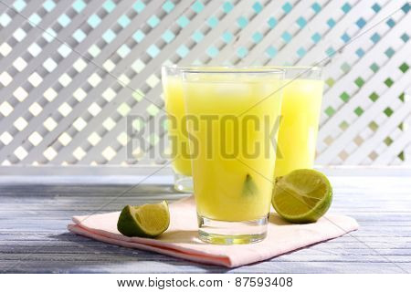 Glasses of cocktails on wooden lattice background