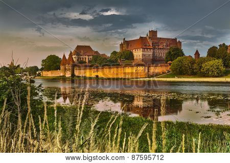 Hdr Image Of Medieval Castle In Malbork At Night With Reflection