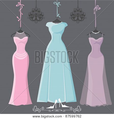 Three retro long bridesmaid dresses hang on ribbons