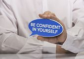 image of self-confident  - Image of a man hand holding blue speech balloon with the text be confident in yourself white shirt and reflexion - JPG