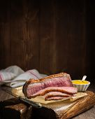 picture of pot roast  - Roast topside of beef sliced on rustic board with pot of mustard - JPG