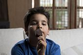 stock photo of pre-adolescent child  - Child enjoying ice cream covered with chocolate at home - JPG