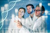 foto of genetic engineering  - Group of geneticists working at media screen - JPG