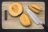 pic of muskmelon  - Chopped fresh musk melon on a cutting board on grey slate background - JPG
