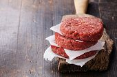 stock photo of hamburger-steak  - Raw Ground beef meat Burger steak cutlets on dark wooden background - JPG