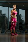 pic of squatting  - Middle Age Woman Performing Dumbbell Squats  - JPG