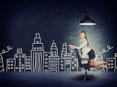 stock photo of kneeling  - Portrait of Young Businesswoman Kneeling on Office Chair Beneath Overhead Light in front of Illustration of City Skyline in Aspirational Concept Image - JPG