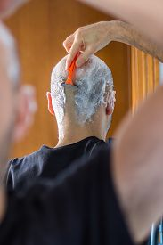stock photo of shaved head  - man who shaves his head with a razor reflected in the mirror - JPG