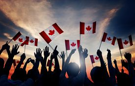 stock photo of waving hands  - Silhouettes of People Holding Flag of Canada - JPG