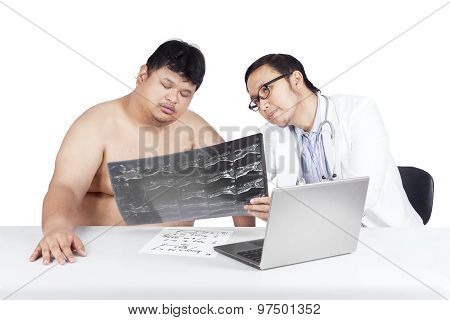 Physician And His Patient Looking At X-ray
