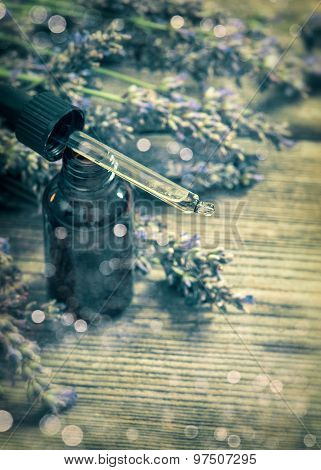 Herbal Oil Essence And Lavender Flowers On Wooden Background. Vintage Style