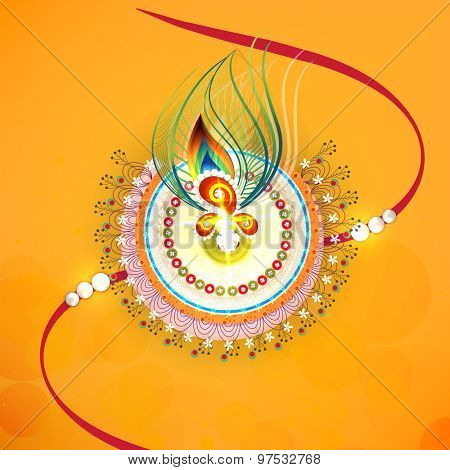 Beautiful creative rakhi with peacock feather on yellow background for Indian festival of brother and sister love, Happy Raksha Bandhan celebration.