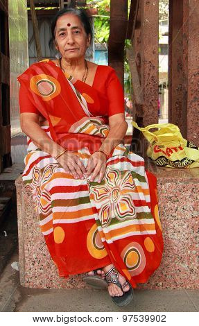 woman in the bright traditional indian dress is sitting outside, Mumbai