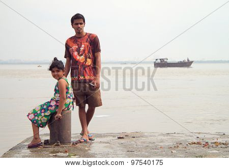 boy and girl are waiting on the wharf in Mumbai