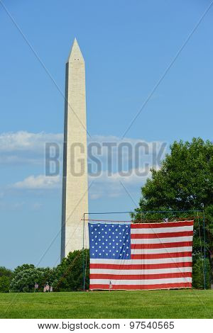 Washington Monument and a large US flag hanged in Constitution Garden - Washington DC, USA
