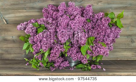 Bouquet Of Lilac Flowers On Wooden Background. Retro Style