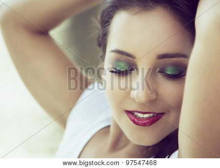 young woman with green eyeshadow and bright makeup, closeup