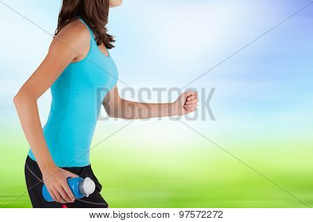 CLose-up of woman runner. Detail on body and arms holding refreshing bottle. Blur motion background. Concept of body training and healthy lifestyle.