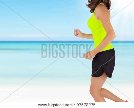 Close-up of woman runner. Detail on body and arms with blur motion beach background. Concept of body training and healthy lifestyle.